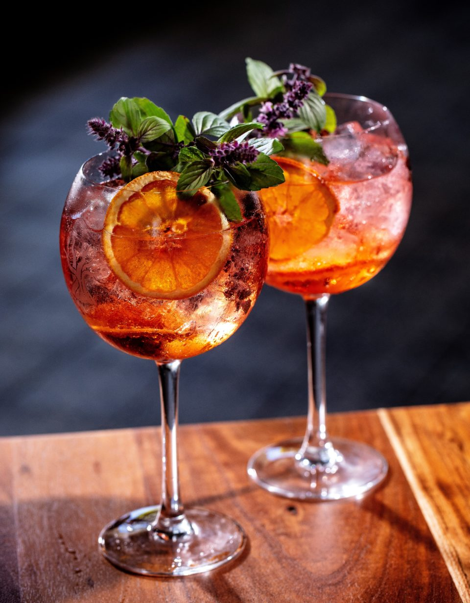 A handcrafted Gin cocktail with orange wheel and blossoms
